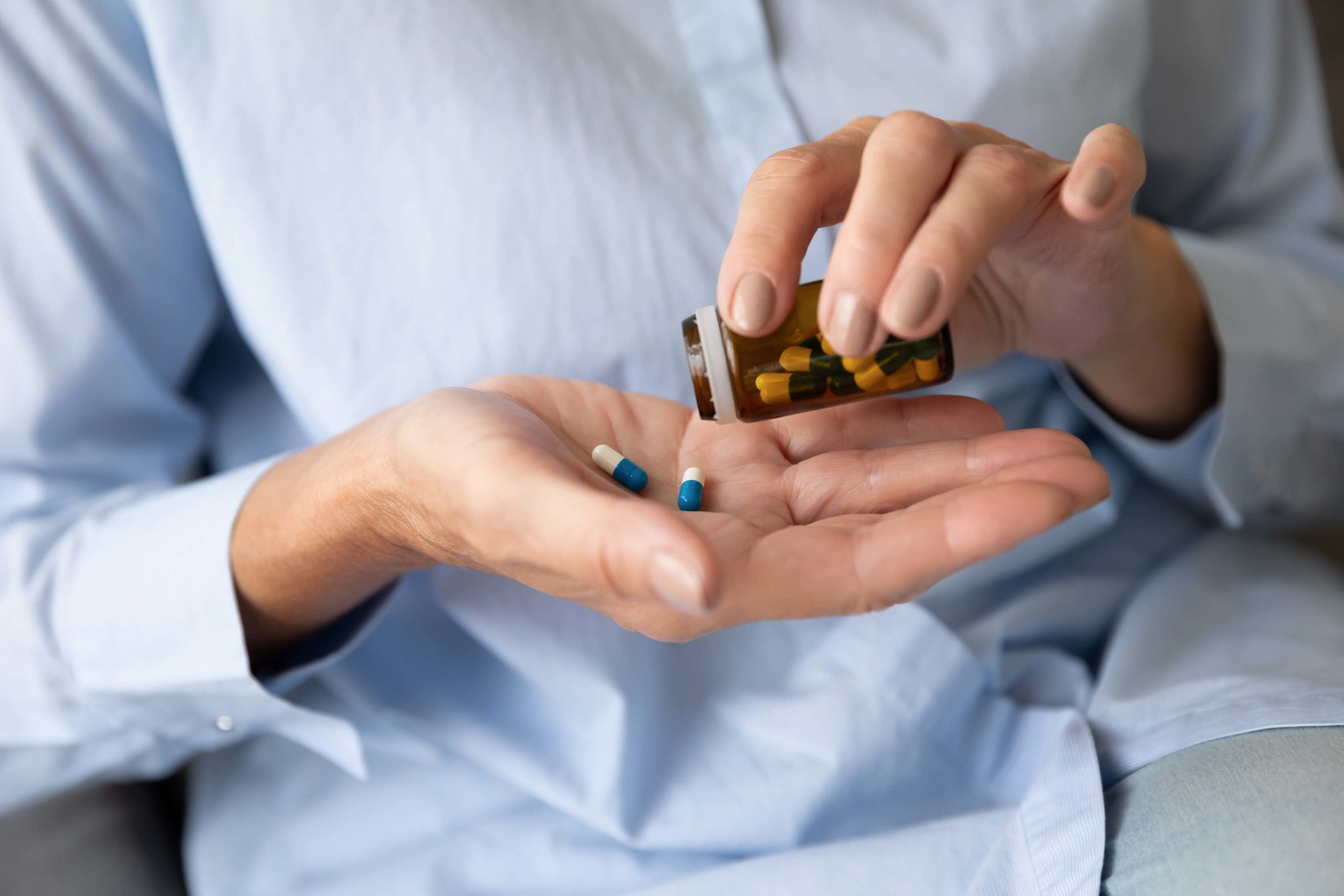 Person tipping a capsule of pills into their hand